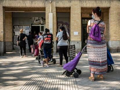 Un grupos de mujeres espera su turno en un local del Banco de Alimentos en el barrio de Orcasitas, Madrid.