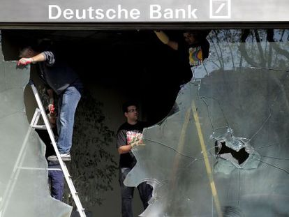 Varios operarios retiran la cristalera rota de una entidad bancaria en los incidentes el día de la huelga general.