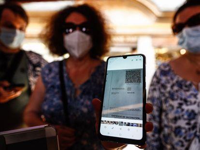 Una mujer muestra su certificado vacunal en un restaurante en Mont-Saint-Michel, en la Normandía francesa.