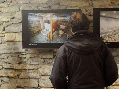 Un hombre observa fotografías de la exposición 'WC: Errealitate desberdinak. Diferentes realidades'.