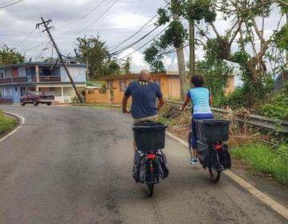 Ciclistas cargando víveres sobre sus vehículos para llegar a lugares alejados, en Puerto Rico.