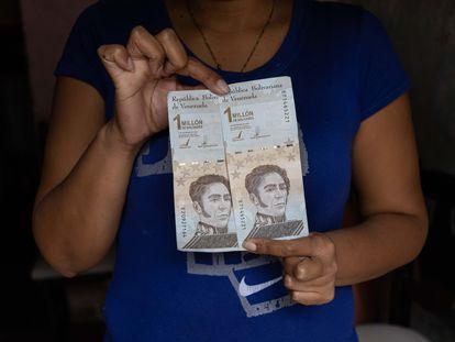Una mujer muestra billetes de bolívares, este jueves en Caracas.