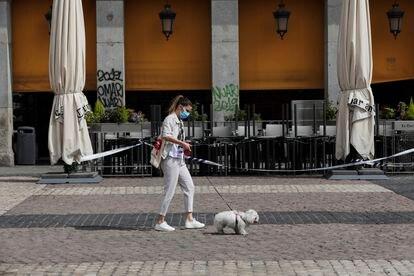 Una mujer protegida con mascarilla camina este sábado por la Plaza Mayor de Madrid.