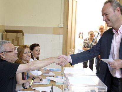 El alcalde de Castellón y candidato a la reelección, Alberto Fabra, saluda a los componentes de la mesa electoral.
