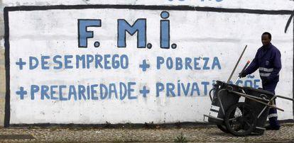 Un barrendero trabaja junto a una pintada crítica con el Fondo Monetario Internacional cerca de Lisboa.
