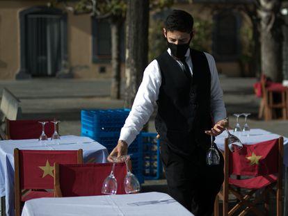 Un camarero prepara las mesas de la terraza para el turno de las comidas.