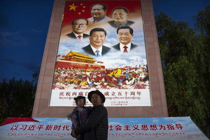 Un hombre posa con una niña frente a un mural que representa al presidente Xi Jinping y otros líderes chinos en la plaza del palacio de Potala, en Lhasa, el 1 pasado de junio