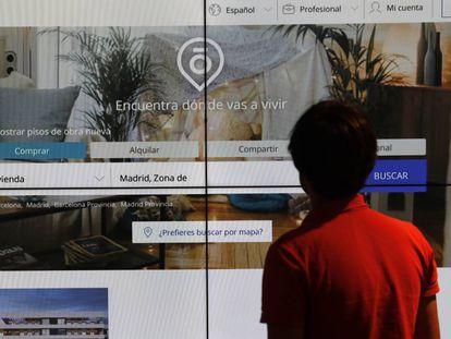 Un hombre consulta un portal inmobiliario en una pantalla gigante, en una imagen de archivo.