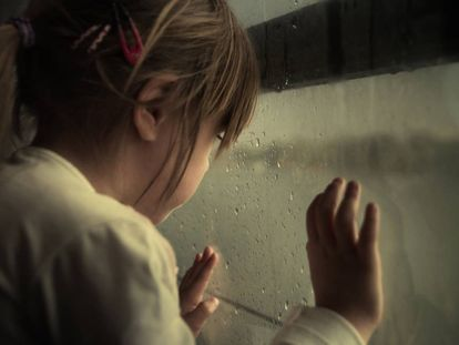 Una niña mira por la ventana.