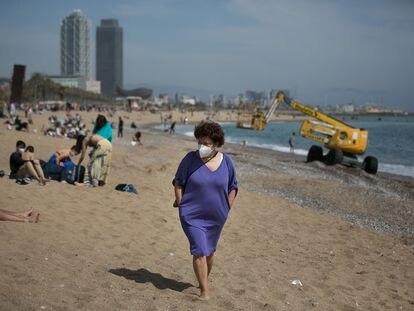 Una mujer pasea con mascarilla por la playa de la Barceloneta, en Barcelona, el pasado miércoles.