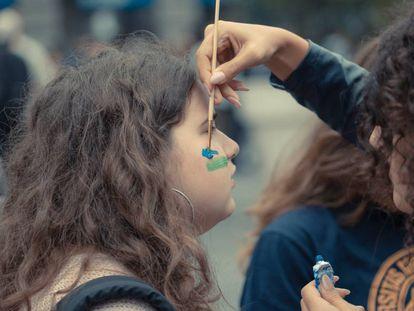 Una joven se pinta para participar en una manifestación contra el cambio climático.