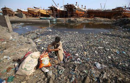 Un hombre busca elementos reciclables entre montones de basura y plástico el mismo día que se celebra el Día Mundial del Medio Ambiente, en Karachi, Pakistán.