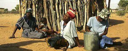 Mujeres de la tribu Basarwa de los Bosquimanos, descansan junto a su cabaña en el asentamiento Kaudawne, a las afueras de la reserva de Kalahari.
