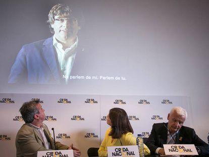 Los diputados Antoni Morra y Gemma Geis y el delegado Ferran Mascarell y en la pantalla, el expresidente Puigdemont.