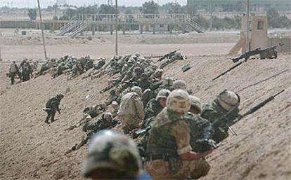 Un grupo de <i>marine</i>s estadounidenses se pone a cubierto tras un talud de tierra para protegerse de los disparos iraquíes en la localidad de Um Qasr, al sur del país.
