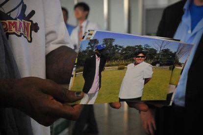 Dennis Rodman muestra una foto suya con Kim Jong-Un en el aeropuerto de Pekín, a su regreso de Corea del Norte en 2013.