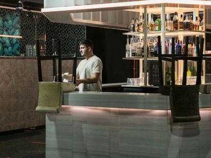Un trabajador de la discoteca Sutton, en Barcelona, acomoda una silla en la barra del local