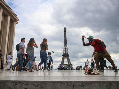 Un grupo de personas, junto a la Torre Eiffel, en París, este viernes.