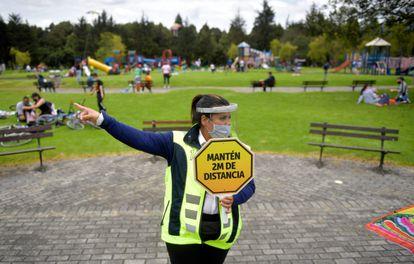 Una vigilante de seguridad con un cartel pidiendo distancia de seguridad, en un parque de Bogotá (Colombia).