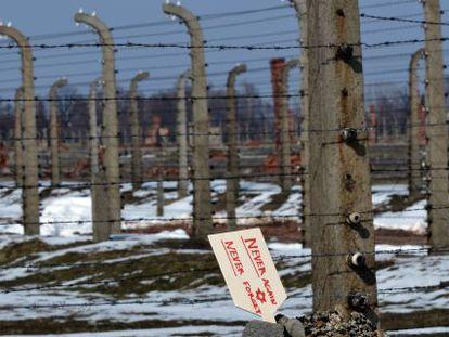 """Una placa que dice """"Nunca de nuevo, nunca olvidar"""" se levanta en unas piedras junto a la verja del campo de Auschwitz-Birkenau."""