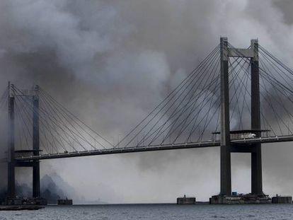 Vista del puente de Rande envuelto en humo del incendio de Fandicosta.