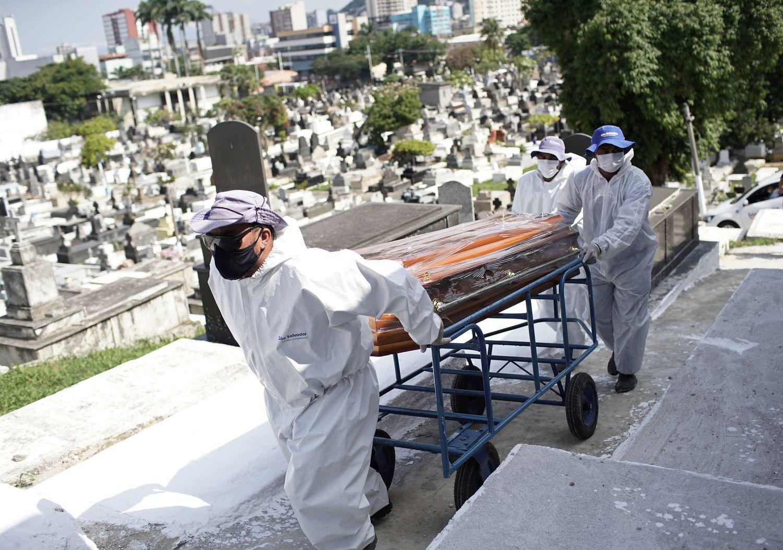 Trabajadores del cementerio de Nova Iguacu en Brasil cargan el ataud de un fallecido por coronavirus.