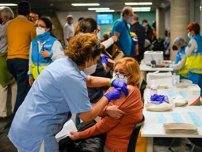 Una sanitaria inocula la vacuna de AstraZeneca a una madrileña en el WiZink Center de Madrid.