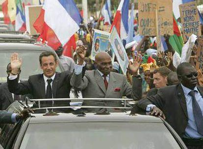Nicolas Sarkozy (izquierda) y el presidente senegalés, Abdoulaye Wade, saludan durante un recorrido por la ciudad de Dakar.