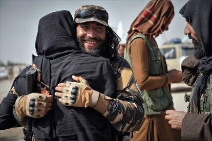 Dos talibanes se saludan en la celebración del homenaje a los muertos en la guerra.