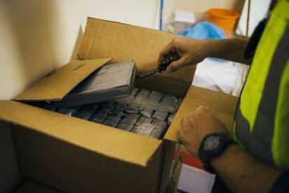 Cajas con droga en el garaje de la vivienda. En la segunda foto, un policía separa uno de los paquetes de cocaína.