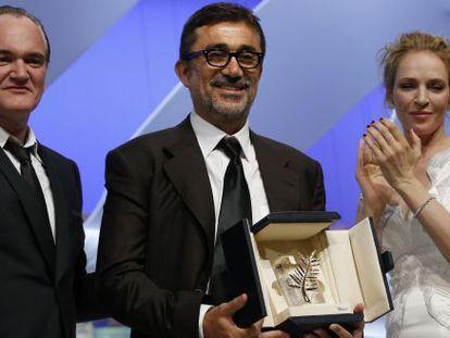 El director turco Nuri Bilge Ceylan  recoge la Palma de oro rodeado de Quentin tarantino y Una Thurman.