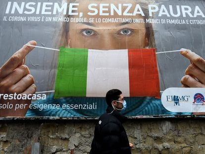 Un hombre con mascarilla pasa por delante de un cartel con indicaciones sobre cómo protegerse del virus, en las calles de Nápoles, el sábado.