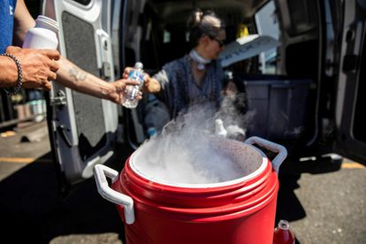 A woman delivers water in Portland on June 27 amid high temperatures.
