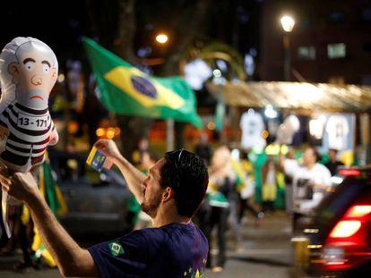 Un hombre sostiene un globo del expresidente Lula da Silva vestido como un reo en una manifestación en Curitiba (Paraná)