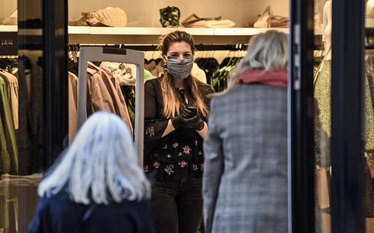 Una dependienta espera la entrada de clientes el primer día de reapertura de las tiendas en Essen, al oeste de Alemania