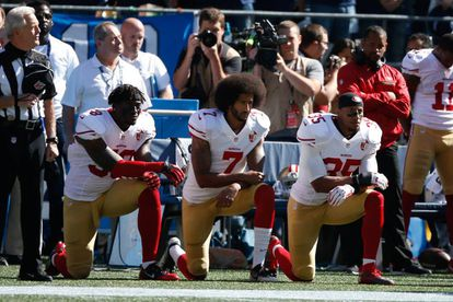 Kaepernick y otros jugadores durante el himno estadounidense