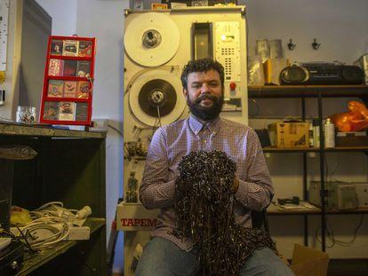 Luis, el dueño de la tienda La Cassetería posa con restos de cintas en su tienda en Madrid.