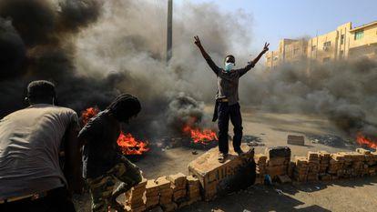 Varios ciudadanos protestan junto a una barricada en el centro de Jartum, este lunes.