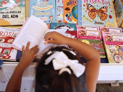 Una niña ojea un libro en una caseta de la Feria del Libro de Madrid.