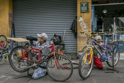 Rolando Morales and Uriel Sánchez work on bicycles in a street workshop in the Centro Histórico neighborhood in Mexico City.