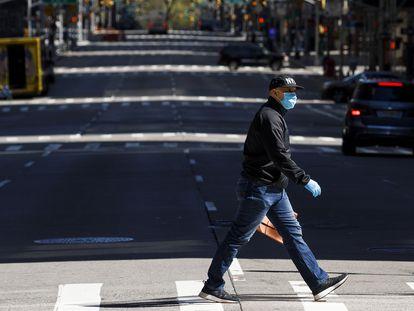Un hombre, con mascarilla, camina por una de las avenidas de Nueva York.