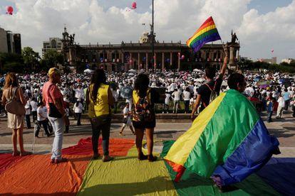 Varios activistas alzan banderas arcoiris en frente de miles de personas que protestan contra el matrimonio homosexual, en Monterrey.
