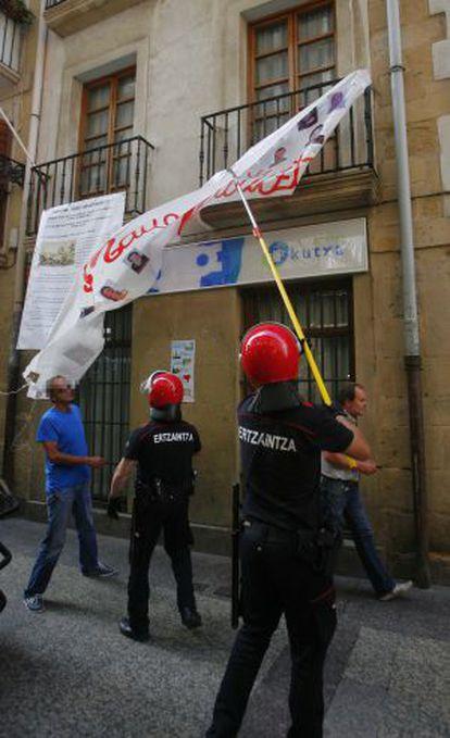 Agentes de la Ertzaintza retiran ayer una pancarta en San Sebastián.