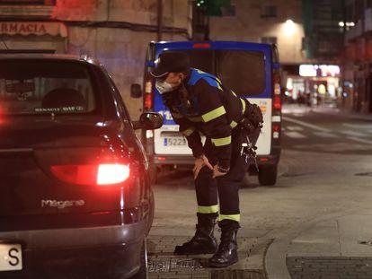 Un policía local se acerca a hablar con ciudadanos que están en un coche en Salamanca, la noche en la que la ciudad vivió el sábado su primer toque de queda dictado por la Junta de Castilla y León para toda la región.