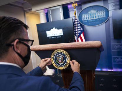 Un miembro de Comunicación de la Casa Blanca coloca el sello presidencial antes de una rueda de prensa de Donald Trump, el pasado 24 de noviembre.