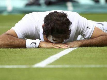 Federer, tendido sobre el césped de la pista central de Wimbledon.