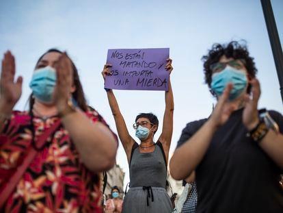 Una mujer sostiene un cartel junto a otros asistentes a una concentración contra la violencia de género, el 6 de agosto en Madrid.