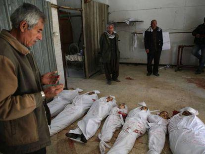 Un hombre reza frente a los cadáveres de varios niños víctimas del último bombardeo del régimen sirio.