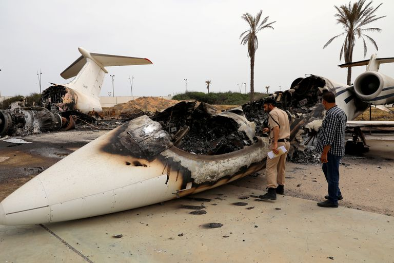 Un policía inspecciona un avión civil alcanzado por las tropas de Jalifa Hafter el 10 de mayo en el aeropuerto de Mitiga, en Trípoli.