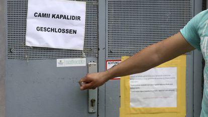Un hombre trata de abrir la puerta de una de las mezquitas cerradas en Viena.